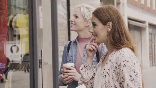 vídeos de stock e filmes b-roll de women shopping, looking into a shopwindow at clothes, then walk on chatting. - ver montras