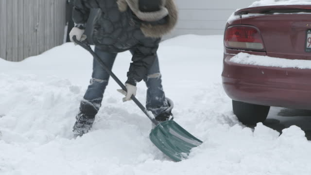 ms women shoveling snow in driveway - driveway stock videos & royalty-free footage