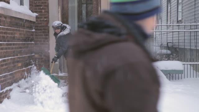 WS Women shoveling snow off porch