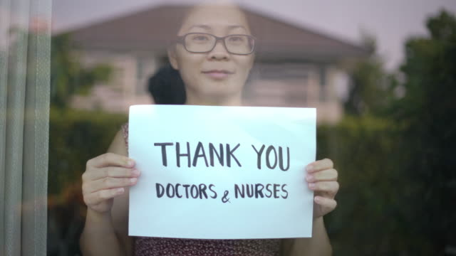 women showing thank you doctors and nurses sign at home for encouraging doctors and nurses in covid-19 coronavirus situation - prevenzione delle malattie video stock e b–roll