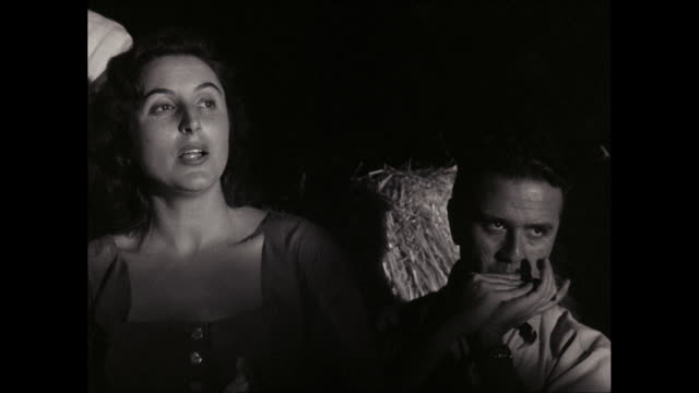 MS Women singing and men playing harmonica at night / United States