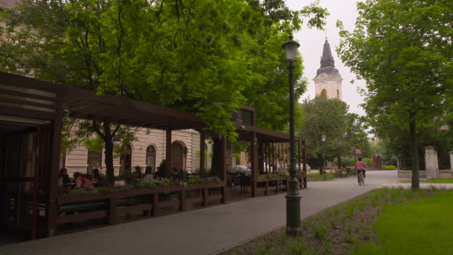women sit at an open air cafž in liberty square in kecskemet - 案内点の映像素材/bロール