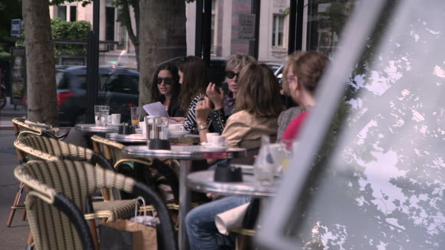 women sit at outdoor seating of a cafe, paris, france. - focus sullo sfondo video stock e b–roll