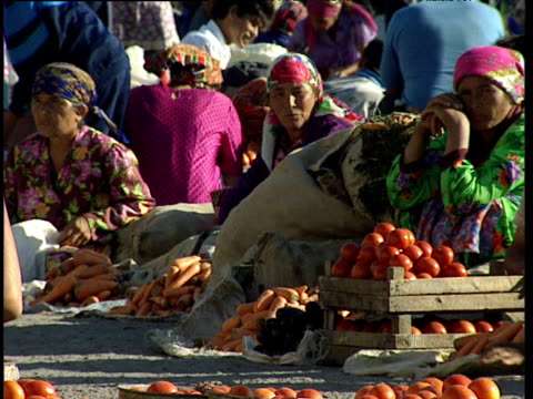 women sit by piles of vegetables at makeshift market bukhara uzbekistan - bukhara stock videos and b-roll footage