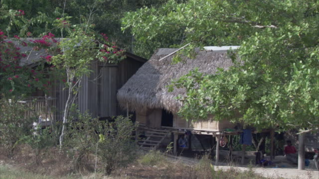 women sit outside a home with a thatched roof. - thatched roof stock videos & royalty-free footage