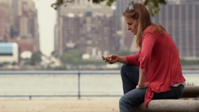 vidéos et rushes de a women sits on a bench in a park and checks her phone.  new york city is behind - text messaging