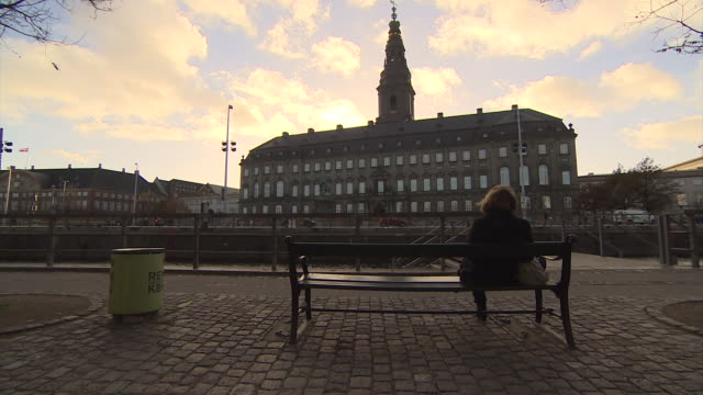 a women sits on a bench opposite the tower of christiansborg palace in copenhagen. - copenhagen video stock e b–roll