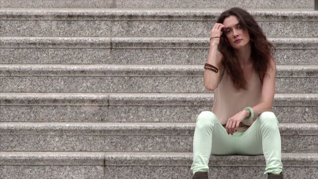 a women sits on granite steps with her head down she fixes her hair and looks around. - granite stock videos and b-roll footage