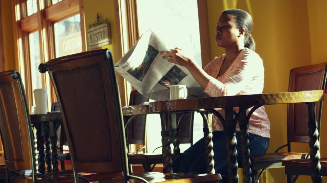 vidéos et rushes de ms la women sitting and reading newspaper in coffee shop / manchester, vermont, usa - manchester vermont