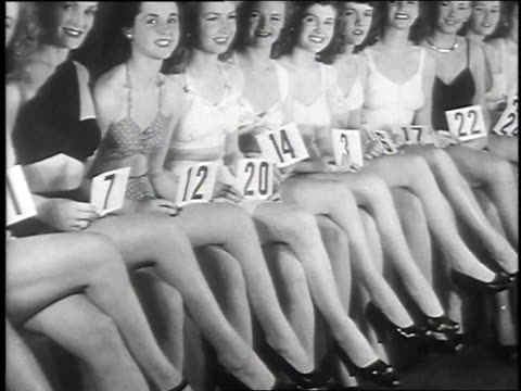 women sitting in a row holding numbers / women crossing their legs / women kneeling on a stage men in the foreground / legs bent - cross legged stock videos & royalty-free footage