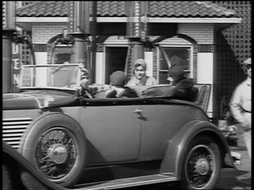 b/w 1929 women sitting in convertible in service station / newsreel - 1920 1929 bildbanksvideor och videomaterial från bakom kulisserna