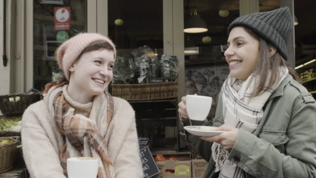 women sitting in outdoor cafe, chatting and laughing. - england stock-videos und b-roll-filmmaterial