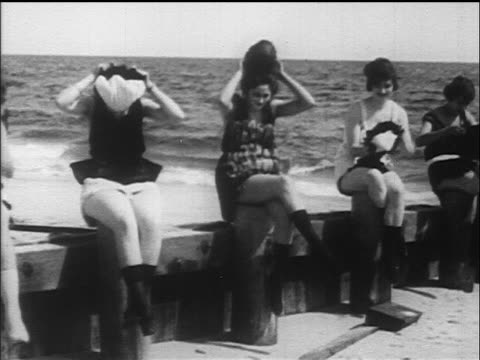 B/W 1917/18 women sitting in swimsuits putting on hats / ocean in background