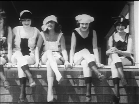 b/w 1917/18 4 women sitting in swimsuits uncrossing + crossing their legs / wave to camera - 1918 stock videos & royalty-free footage