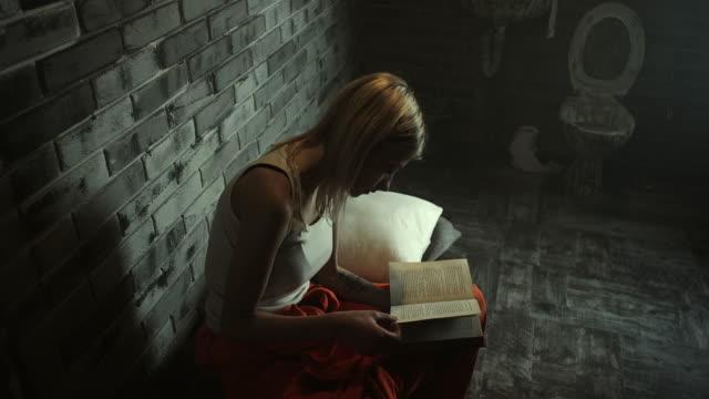 vídeos de stock, filmes e b-roll de mulheres sentadas na cama na cela da prisão e lendo um livro - bíblia