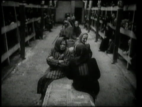 women sitting on benches and lying huddled together in bunks / oswiecim germany - concentration camp stock videos & royalty-free footage