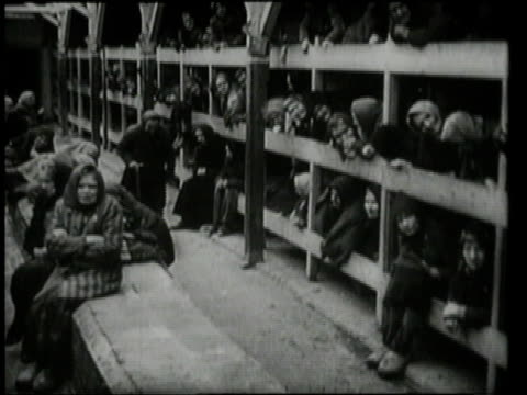 women sitting on benches and lying in bunks, while one woman limps past / oswiecim, germany - concentration camp stock videos & royalty-free footage
