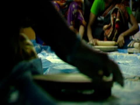 vídeos de stock, filmes e b-roll de women sitting on floor rolling dough for roti - rolo de pastel