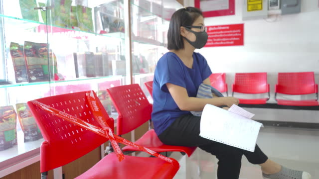 women sitting on the chairs are waiting for queue in the post office - job search stock videos & royalty-free footage