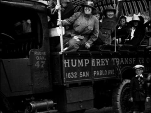 B/W 1922 women sitting on truck headed to vacation waving to camera / Oakland, California / newsreel