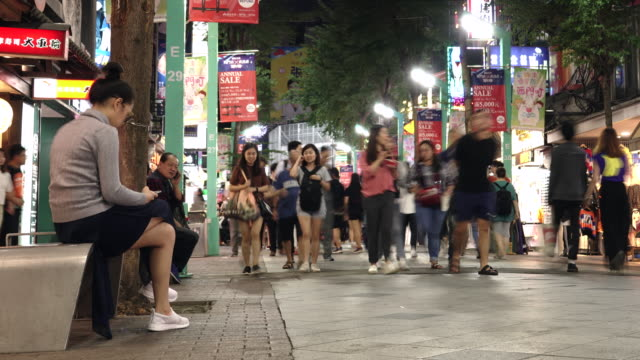 women sitting taipei city ximen area night time traffic time lapse - taipei stock videos & royalty-free footage