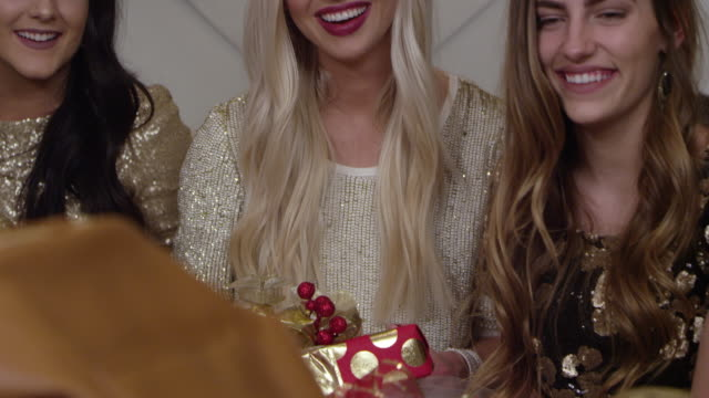 Women smiling while opening gifts at a Holiday Christmas party