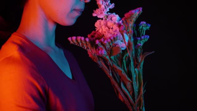 stockvideo's en b-roll-footage met vrouwen ruiken de geur van bloemen - paars