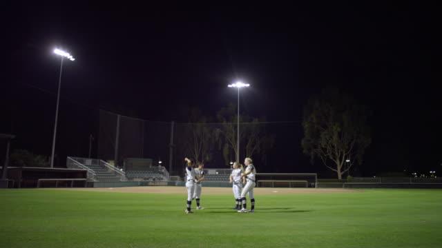 vídeos y material grabado en eventos de stock de ws 4 women softball players standing stretching arm and talking in ground / riverside, california, united states - sófbol