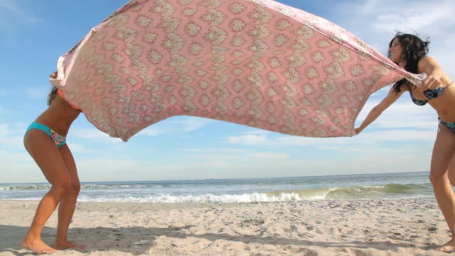 Women spreading blanket on beach