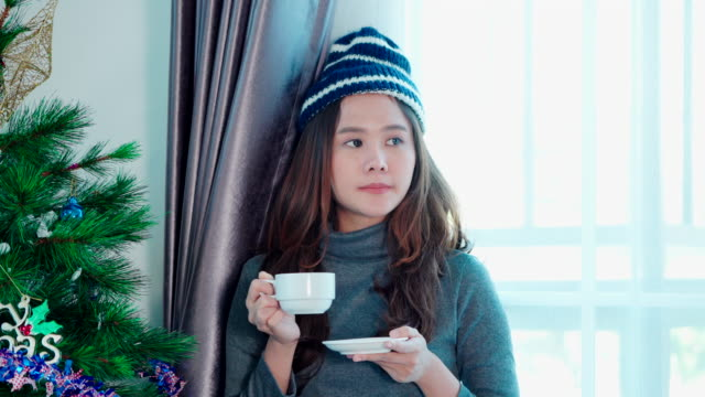 女性は、新年の早い時期に教会の早い時期にリビングルームで涼しく快適な空気の中で朝にコーヒーを飲みに立っています。 - 交代点の映像素材/bロール