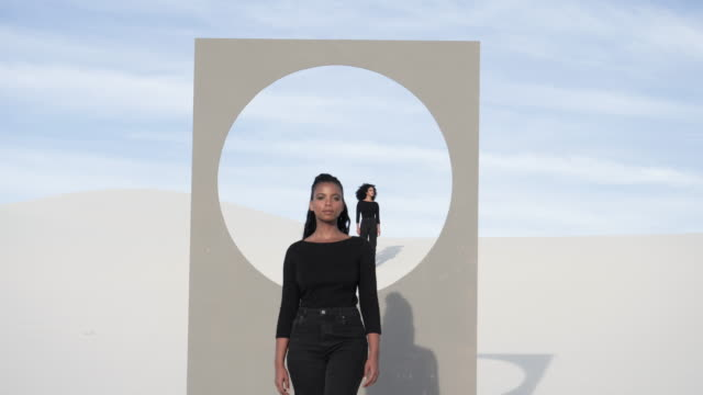 women stand near placard with circle window frame in desert - imagination stock videos & royalty-free footage