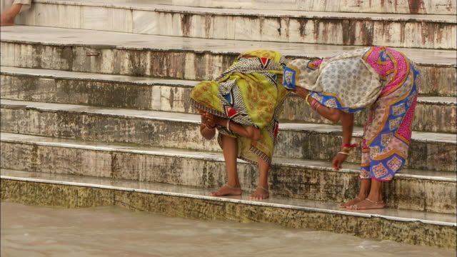 women stand on stairs and wash in the ganges river. available in hd. - パレオ点の映像素材/bロール