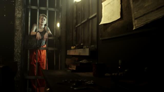 Frauen stehen an Tür in Gefängniszelle mit ihren Händen durch Gitterstäbe