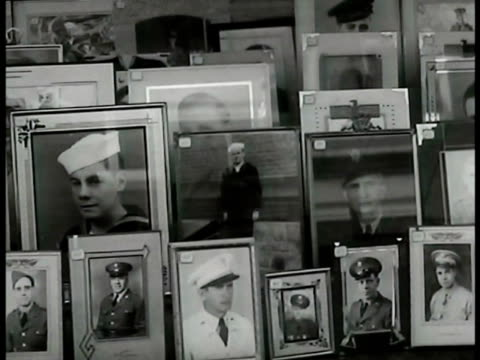 women standing in front of hometown shop window w/ displayed photographs of soldiers servicemen cu soldier elder woman standing by window cu... - hometown stock videos and b-roll footage
