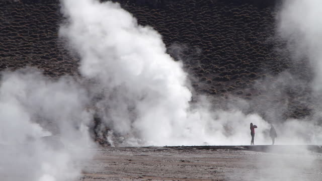 ms women standing in geyser fields and taking pictures and admiring scene of vapour coming out from ground  / geiser del tatio, atacama desert, chile - geyser stock videos and b-roll footage