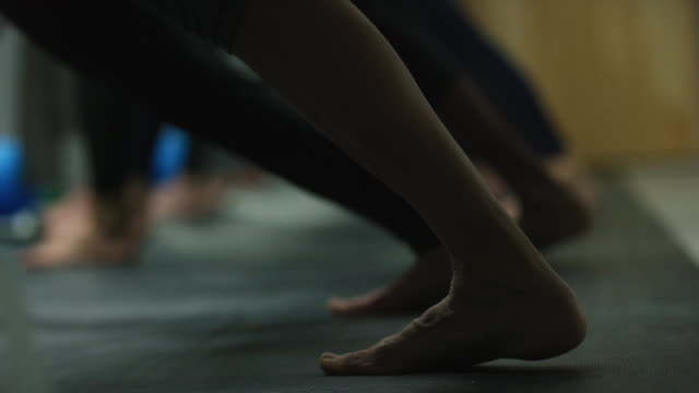 women stretch out their calf muscles in a fitness class at an exercise studio - calf stock videos & royalty-free footage