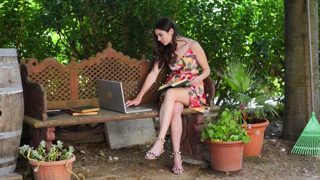 vídeos y material grabado en eventos de stock de women studies and uses the computer sitting in a bench in the garden - brown hair