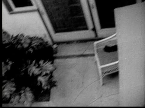 vídeos de stock, filmes e b-roll de 1937 b/w os ws women sunbathing on patio/ pan ws man (hal richardson) hiding on room and taking photos of her - espreitando