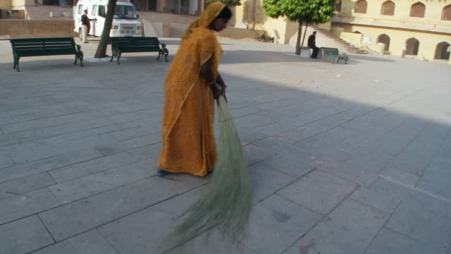 Women sweeping street with twig broom