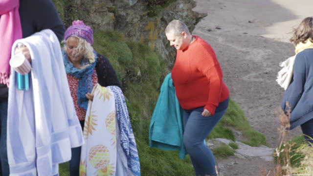4 women swimmers walking up the coastal path from the beach. - only mature women stock videos & royalty-free footage