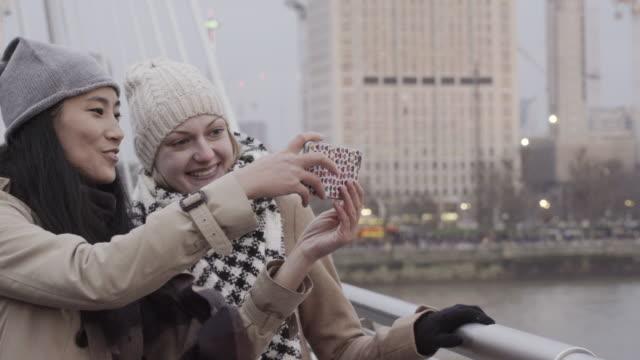 Women take photographs, standing on bridge overlooking Thames river.