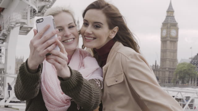 Women take Selfies with smart phone in front of Big Ben at river Thames embankment, London.