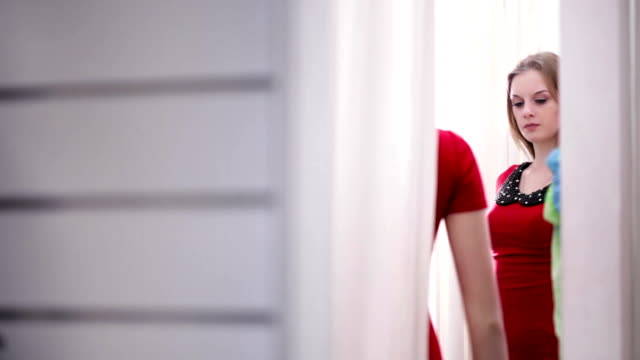 Women takes on red dress in clothing store fitting room