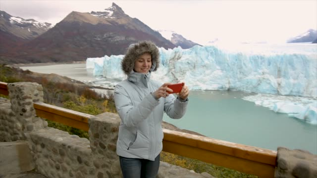 women takes selfie photo at perito moreno glacier in cold weather - argentina stock videos & royalty-free footage