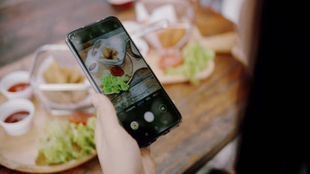 cu : women taking photo of food in restaurant - photographing stock videos & royalty-free footage