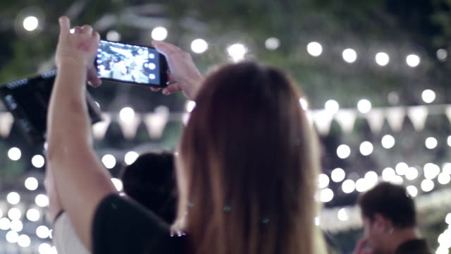 Women Taking Photo With Smart Phone In a Wedding Party At Night