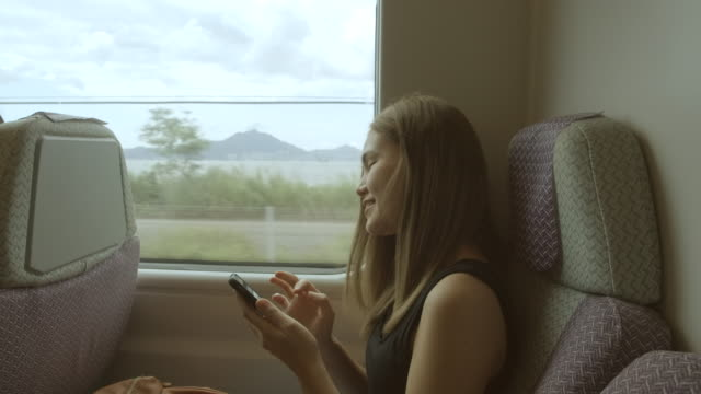 women taking pictures of external views while traveling on a high speed train - rail transportation stock videos & royalty-free footage