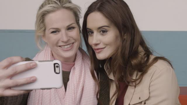 Women taking Selfies on smart phone.