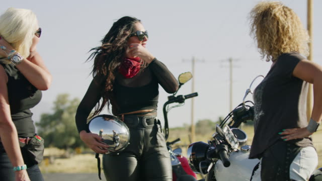 women talking and high-fiving after riding motorcycles / payson, utah, united states - ヘルメット点の映像素材/bロール