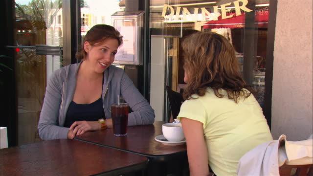 vidéos et rushes de women talking and holding hands at outdoor cafe - fille de